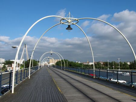 southport, merseyside, united kingdom - 28 july 2019: the historic pier in southport merseyside with people walking towards the town and the suspension bridge and buildings visible behind trees