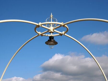 close up of the ornate victorian lights on the historic southport pier against a blue summer sky with clouds