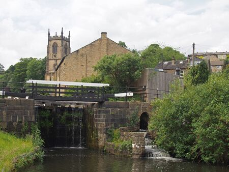 lock gates on the canal in sowerby bridge in west yorkshire with the historic christ church building surrounded by trees