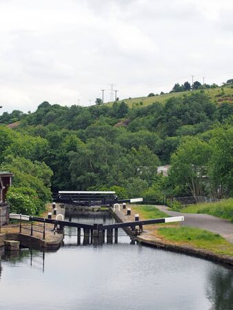 wooden lock gates on the calder and hebble navigation canal in front of the basin in sowerby bridge west yorkshire surrounded by trees and buildings 写真素材