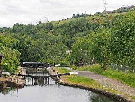 wooden lock gates on the calder hand hebble navigation canal in front of the basin in sowerby bridge west yorkshire surrounded by trees and buildings