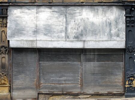 the front of an abandoned store on a street with closed dirty rusting metal shutters over the shop front and door