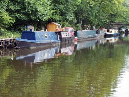 narrow boats and barges moored on the rochdale canal in hebden bridge surrounded by green summer trees and a stone footbridge