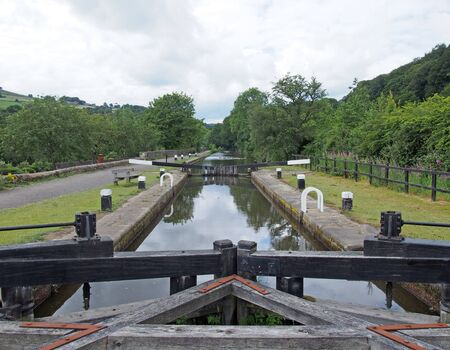 old wooden lock gates on the rochdale canal outside mytholmroyd surrounded by trees and fields in the calder valley in west yorkshire