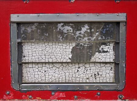 an old scruffy caravan window with steel frame and slatted windows with cracked old white paint with a red surround with rivets