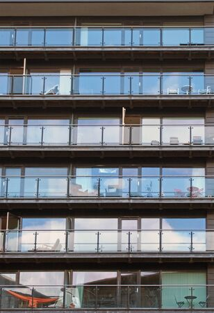 rows of apartments in a large modern building with glass balconies and outdoor furniture and sky reflected in the windows