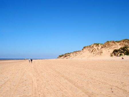 sefton, merseyside, united kingdom - 27 june 2019: people walking on the beach with grass on the top of tall sand dunes on the sefton coast in merseyside with blue summer sea and sky 写真素材