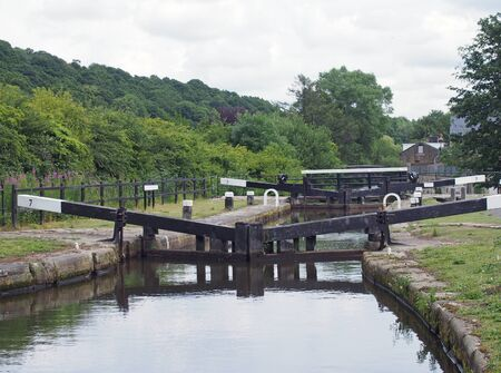 broadbottom lock on the rochdale canal on the outskirts of mytholmroyd west yorkshire with summer trees lining the valley and buildings of the town in the distance