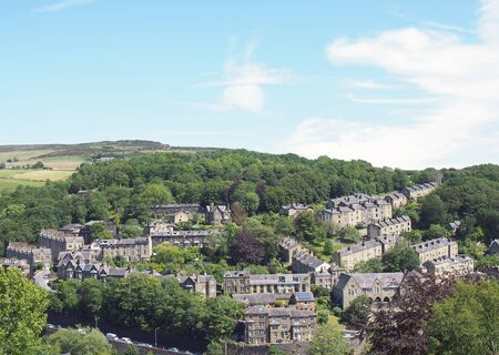 a scenic aerial view of the town of hebden bridge in west yorkshire with streets of stone houses and roads between trees and a blue summer cloudy sky
