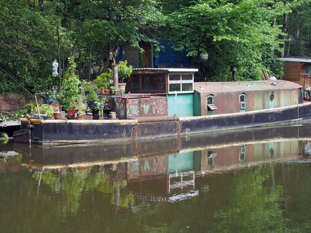 an old rusty narrow boat reflected in the water and surrounded by trees on the rochdale canal in hebden bridge west yorkshire