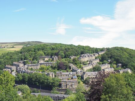 a scenic aerial view of the town of hebden bridge in west yorkshire with streets of stone houses and roads between woodland trees and a blue summer sky