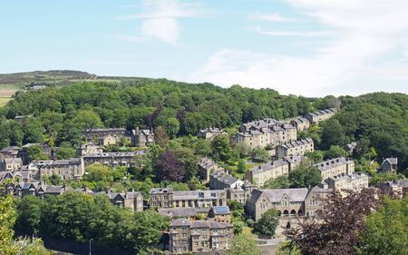 a scenic aerial view of the town of hebden bridge in west yorkshire with hillside streets of stone houses and roads between trees and a blue summer sky