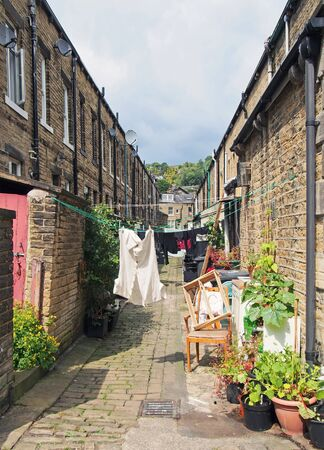 a back alley between streets with rows of traditional stone houses in hebden bridge west yorkshire with washing drying on lines and pot plants in bright summer sunshine