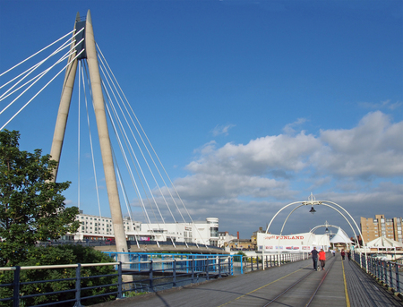 southport, merseyside, united kingdom - 28 june 2019: people walking along along the pier in southport merseyside on a bright summer day with the suspension bridge and buildings with a blue cloudy sky