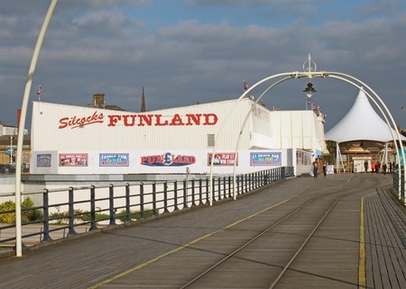 southport, merseyside, united kingdom - 28 june 2019: people walking around the entrance to southport pier in merseyside with a carousel and amusement arcade