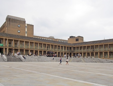 halifax, west yorkshire, united kingdom - 12 july 2019: people walking and sat on the steps of the piece hall in halifax west yorkshire