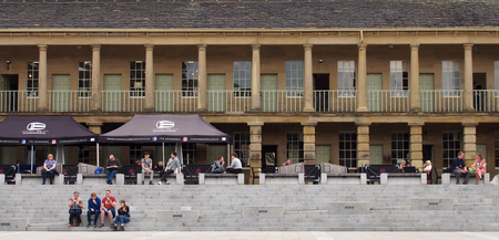 halifax, west yorkshire, united kingdom - 12 july 2019: people sat on the steps of the piece hall in halifax west yorkshire with people shopping and sat in cafes and bars