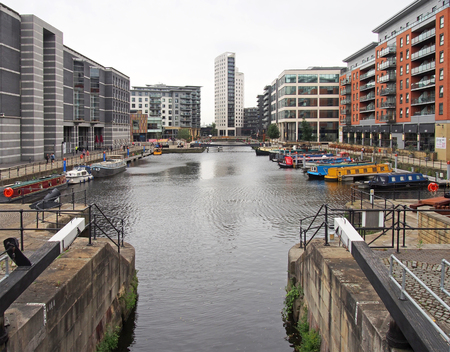 leeds, west yorkshire, united kingdom - 4 july 2019: a view of leeds dock from the lock gates with houseboats moored next to waterside buildings