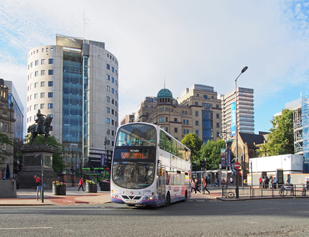 leeds, west yorkshire, united kingdom - 4 july 2019: a bus in city square in leeds west yorkshire with people walking past city buildings and monuments in bright summer sunshine