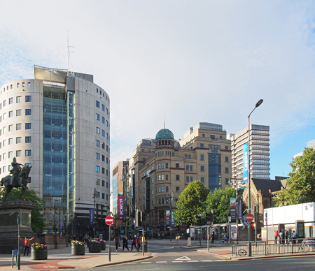 leeds, west yorkshire, united kingdom - 4 july 2019: city square in leeds west yorkshire with people walking past city buildings and monuments in bright summer sunshine