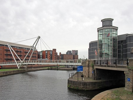 leeds, west yorkshire, united kingdom - 4 july 2019: knights bridge crossing the river aire and canal in leeds with waterside apartments and the royal armouries museum next to the dick entrance