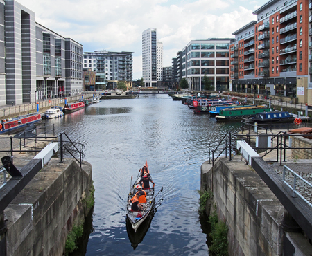 leeds, west yorkshire, united kingdom - 16 july 2019: leeds dock from the lock gates with houseboats and buildings with a rowing boat passing through