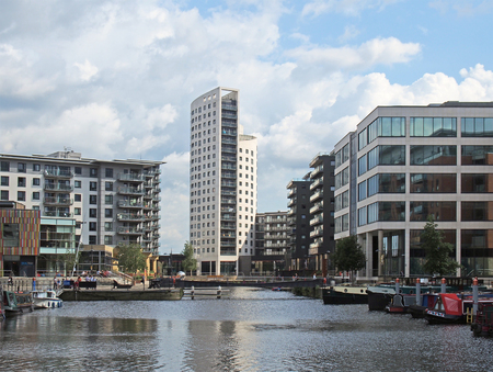 leeds, west yorkshire, united kingdom - 16 july 2019: a view of of leeds dock with clarence house surrounded by modern apartment developments and bars with moored houseboats and blue cloudy sky