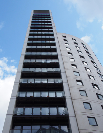 leeds, west yorkshire, united kingdom - 16 july 2019: clarence house a 218 foot tall modern apartment and retail building in the leeds dock area against a blue cloudy sky