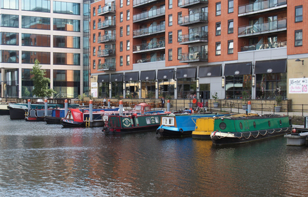 leeds, west yorkshire, united kingdom - 16 july 2019: a view of of leeds dock houseboats and barges moored next to apartment developments and a restaurant