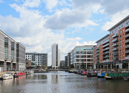 leeds, west yorkshire, united kingdom - 16 july 2019: a view of of leeds dock with modern apartment developments and bars with moored houseboats and blue cloudy sky
