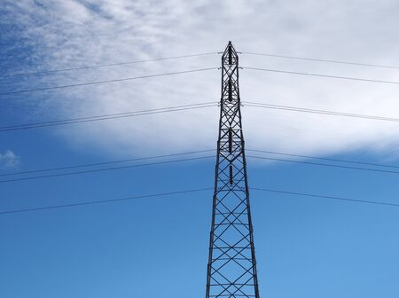 a tall steel electricity pylon with cables against a blue sky with white clouds