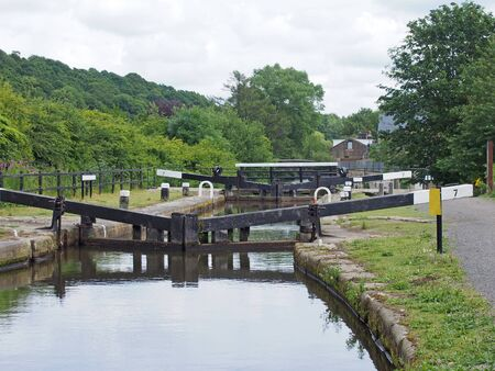 lock gates on the rochdale canal in mytholmroyd west yorkshire with buildings surrounded trees along the calder valley