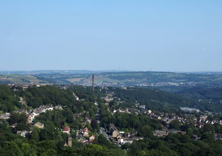 a panoramic view of the town of west yorkshire from above with streets and houses surrounded by trees and fields and the historic wainhouse tower on a hillside Reklamní fotografie