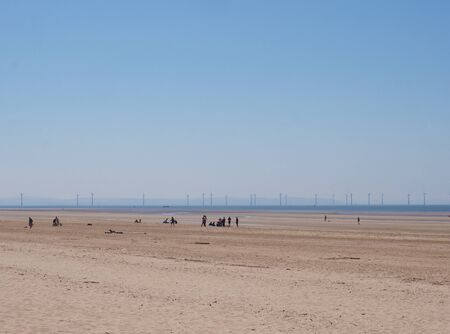 a view of a large flat sand covered summer beach in formby merseyside with unrecognizable people in the middle distance and windmills on the horizon