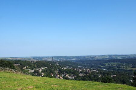 a panoramic view of halifax from above surrounded by Fields and pennine hills and a blue summer sky