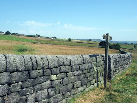 rural scene with a long stone wall and wooden signpost next to a gate in hillside meadows with farmhouses and hills in the distance in blackshaw head in west yorkshire Stockfoto