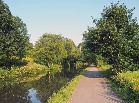 a long straight path along a canal in summer with trees reflected in the water in bright summer sunlight near luddenden in west yorkshire Stockfoto