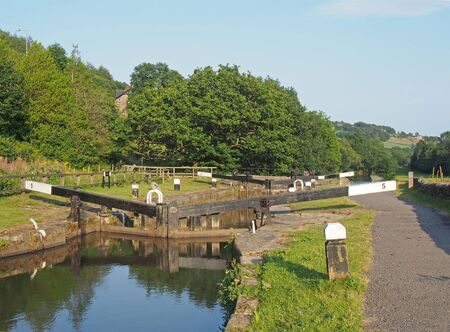 lock gates in the in the calder valley in brearley on the rochdale canal between luddenden foot and mytholmroyd surrounded by summer trees Stockfoto