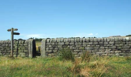 a stone wall with gate next to a wooden signpost in a green field in a bright sunlit landscape in calderdale west yorkshire
