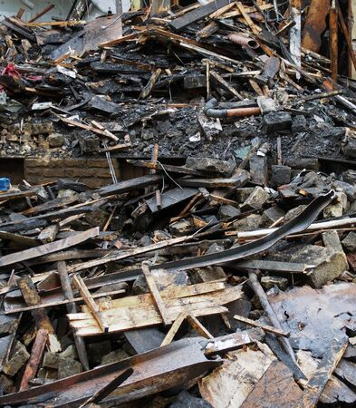 a heap of burned and scattered bricks beams and rubble after a fire in a large building 版權商用圖片