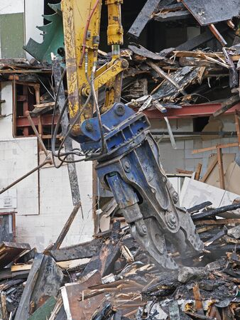 a large excavator demolition claw removing debris and rubble from a wrecked building destroyed by fire
