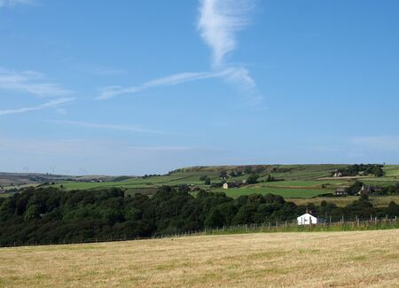 a cut summer hay meadow surrounded by green fields and farmhouses with a blue sunlit sky above the village of luddenden in calderdale west yorkshire