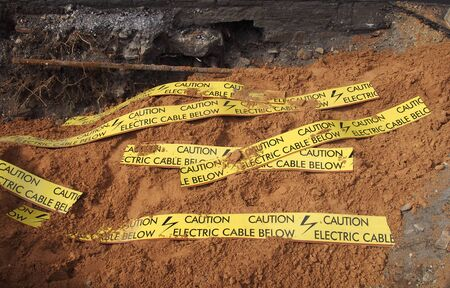 yellow tape signs warning of buried electric cable below in a trench being excavated during roadwork and building construction Фото со стока