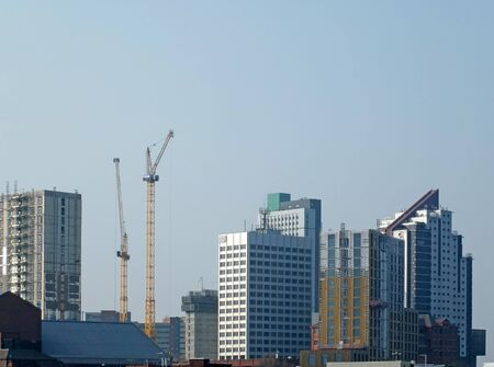 leeds, west yorkshire, england - 17 april 2019: tall tower cranes working on new high rise buildings under construction in leeds city centre