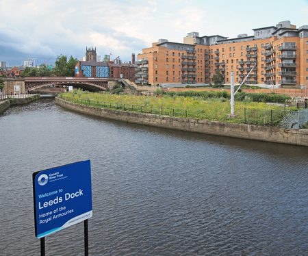 leeds, west yorkshire, united kingdom - 4 july 2019: riverside view of leeds near the dock entrance with sign next to the canal and waterside apartment with the minster and city centre in the distance