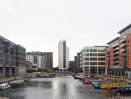 leeds, west yorkshire, united kingdom - 4 july 2019: a view of leeds dock from with houseboats moored next to waterside buildings