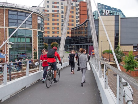 leeds, west yorkshire, united kingdom - 4 july 2019: people walking and cycling across millennium bridge in leeds with waterside buildings and bars