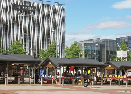 leeds, west yorkshire, united kingdom - 16 july 2019: leeds outdoor market with people shopping at traditional stalls selling clothing and food in front of the modern victoria quarter shopping centre  報道画像