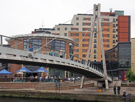 leeds, west yorkshire, united kingdom - 4 july 2019: the millennium footbridge in leeds with people drinking at an outside bar after work and men fishing in the river