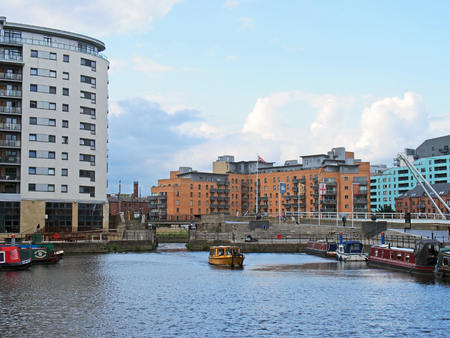leeds, west yorkshire, united kingdom - 16 july 2019: a view of the lock gates at leeds dock with a yellow water taxi and houseboats moored along the dockside